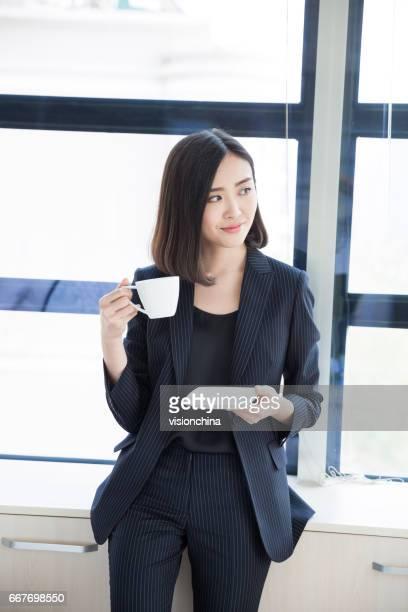 businesswoman standing near by window in office