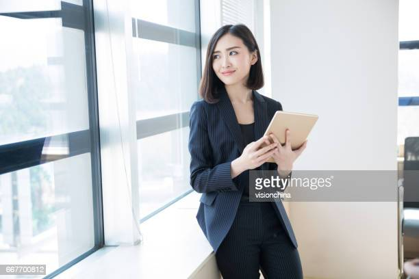 businesswoman standing near by window in office - chinese ethnicity stock pictures, royalty-free photos & images