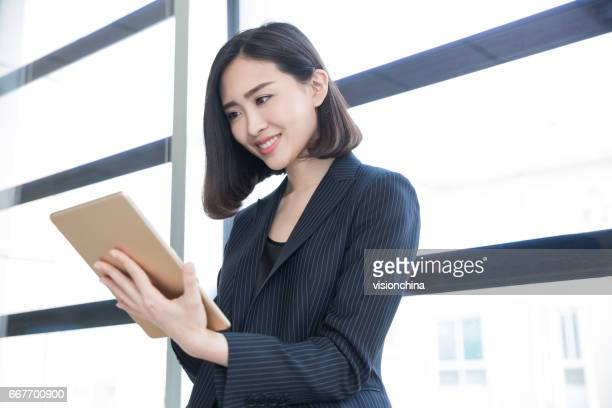 businesswoman standing near by window in office