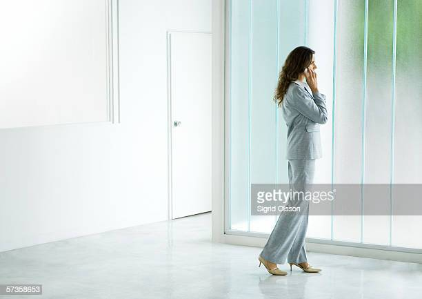 businesswoman standing near window, using cell phone - erker stockfoto's en -beelden