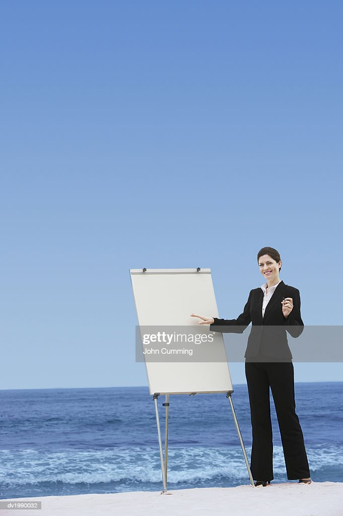 Businesswoman Standing Next to a Blank Flip Chart on a Beach : Stock Photo