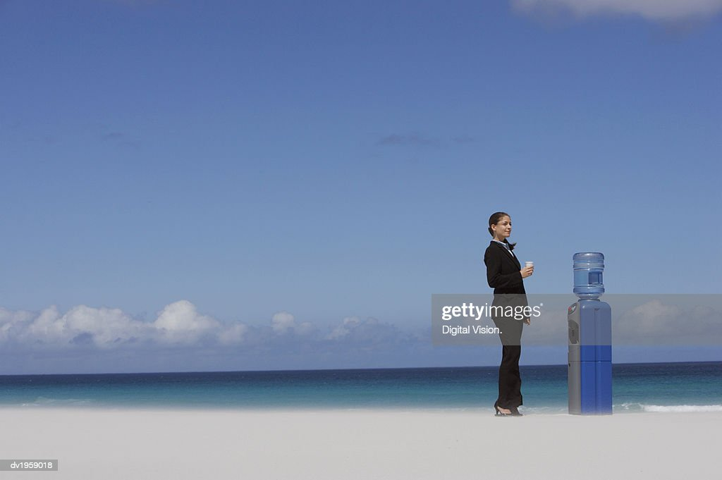 Businesswoman Standing Next to a Water Cooler : Stock Photo