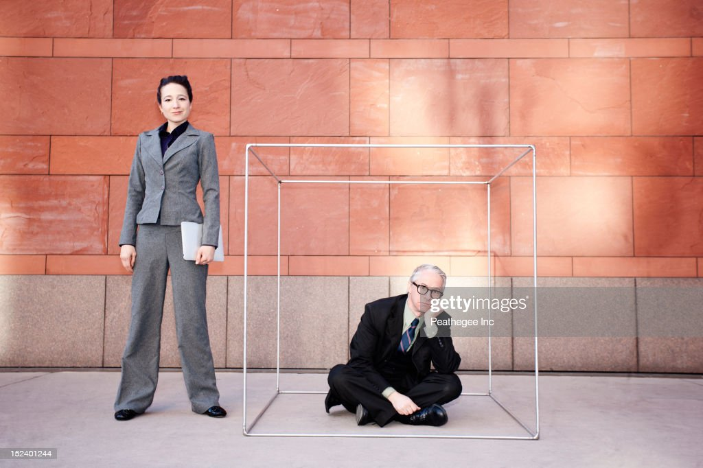 Businesswoman standing next to co-worker in box : Stock Photo