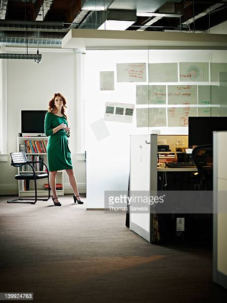 Businesswoman standing next to glass wall