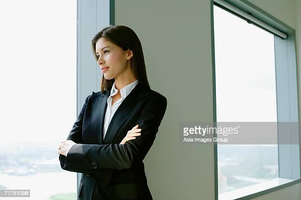Businesswoman standing next to window in conference room, arms crossed