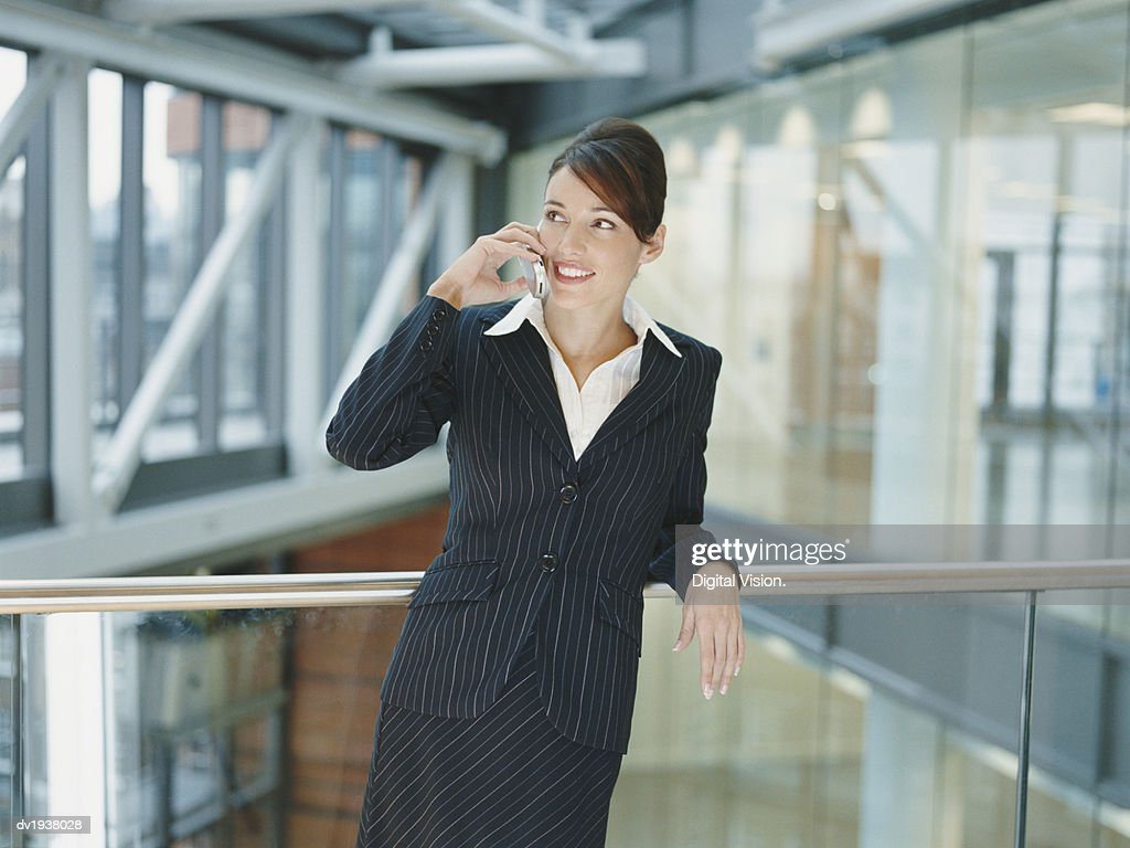 Businesswoman Standing on a Balcony in an Office Building Using a Mobile Phone : Stock Photo