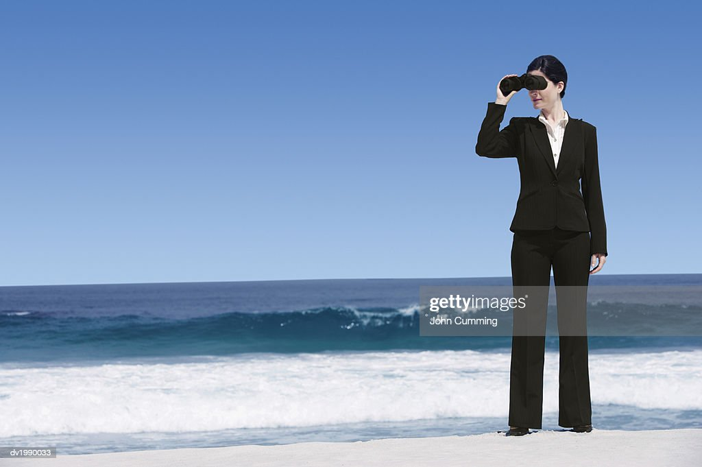 Businesswoman Standing on a Beach Looking Through Binoculars : Stock Photo