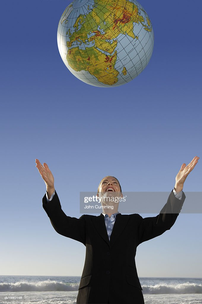Businesswoman Standing on a Beach Throwing a Globe in the Air : Stock Photo