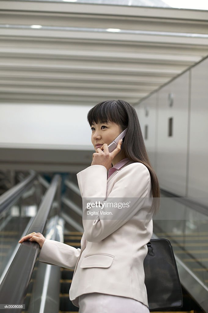 Businesswoman Standing on an Escalator Using a Mobile Phone : Stock Photo
