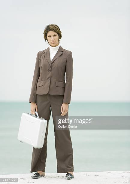 Businesswoman standing on beach holding briefcase