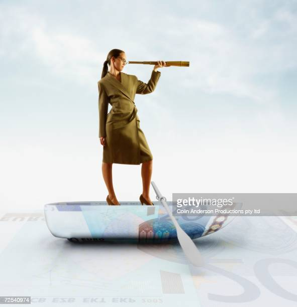 Businesswoman standing on boat made of Euro and looking through spyglass