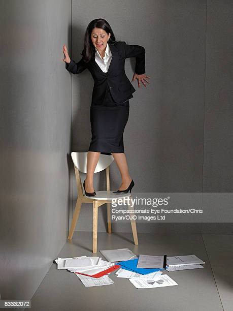 Businesswoman standing on chair