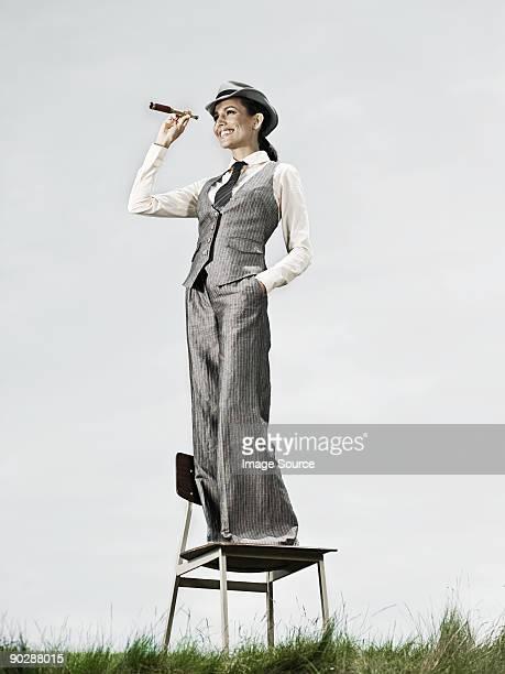 femme d'affaires debout sur une chaise avec un télescope - longue vue photos et images de collection