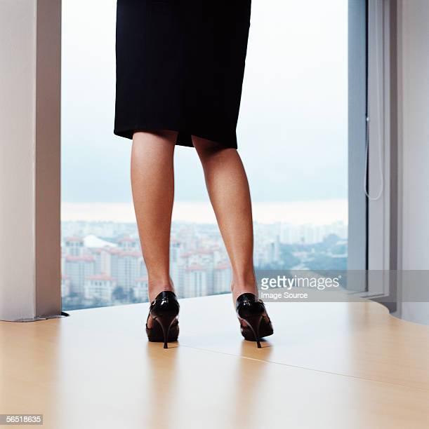 Businesswoman standing on desk