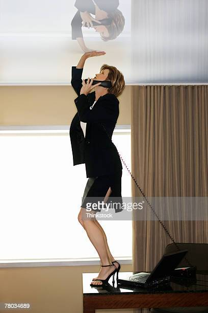 Businesswoman standing on desk touching glass ceiling