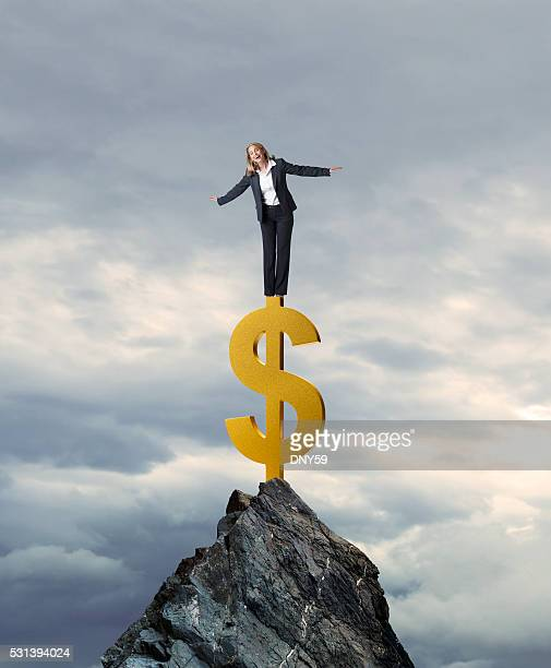 Businesswoman Standing On Dollar Sign On Mountian Top