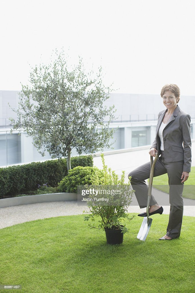 Businesswoman standing on garden spade : Stock-Foto
