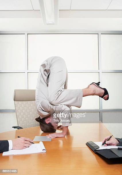 Businesswoman standing on head during meeting