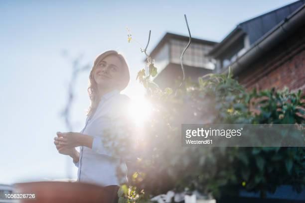 businesswoman standing on her urban rooftop garden - nachhaltigkeit stock-fotos und bilder