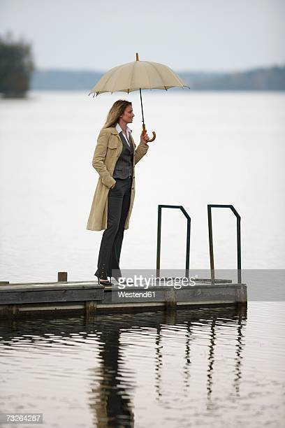 businesswoman standing on jetty, holding umbrella, side view