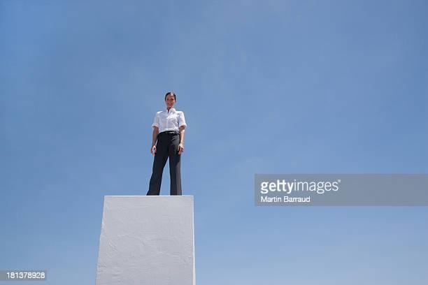 Businesswoman standing on pedestal outdoors