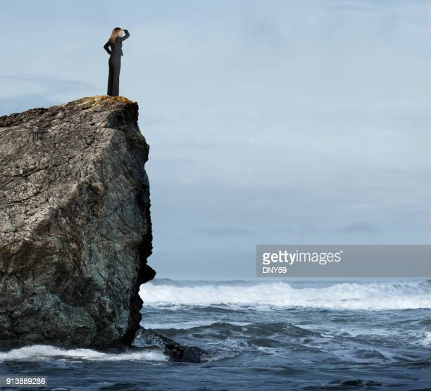 Businesswoman Standing On Rocky Cliff Overlooking Stormy Seas