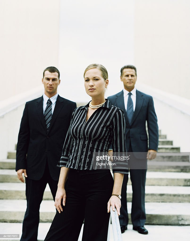 Businesswoman Standing on Steps in Front of Two Other Business Executives : Stock Photo