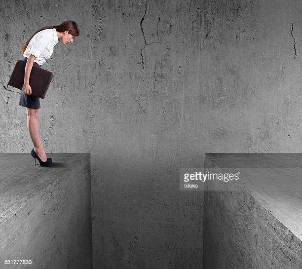 Businesswoman standing on the edge of wall and look down