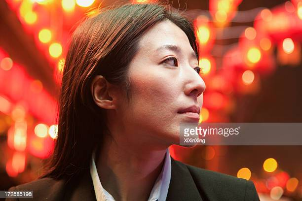 Businesswoman standing on the street, red lanterns on the background