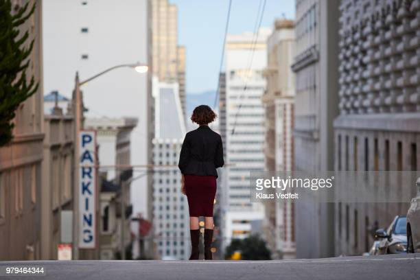 Businesswoman standing on top of steep San Francisco street and looking out