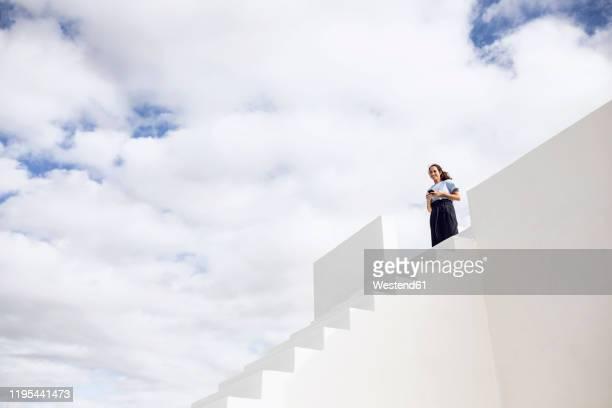 businesswoman standing on white stairs, using smartphone - bien vestido fotografías e imágenes de stock