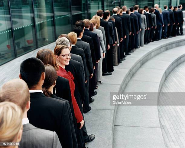 businesswoman standing out in a line of business people waiting outdoors on a step - lining up stock pictures, royalty-free photos & images