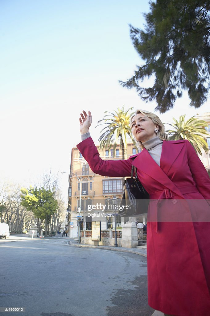 Businesswoman Standing Outdoors and Hailing : Stock Photo