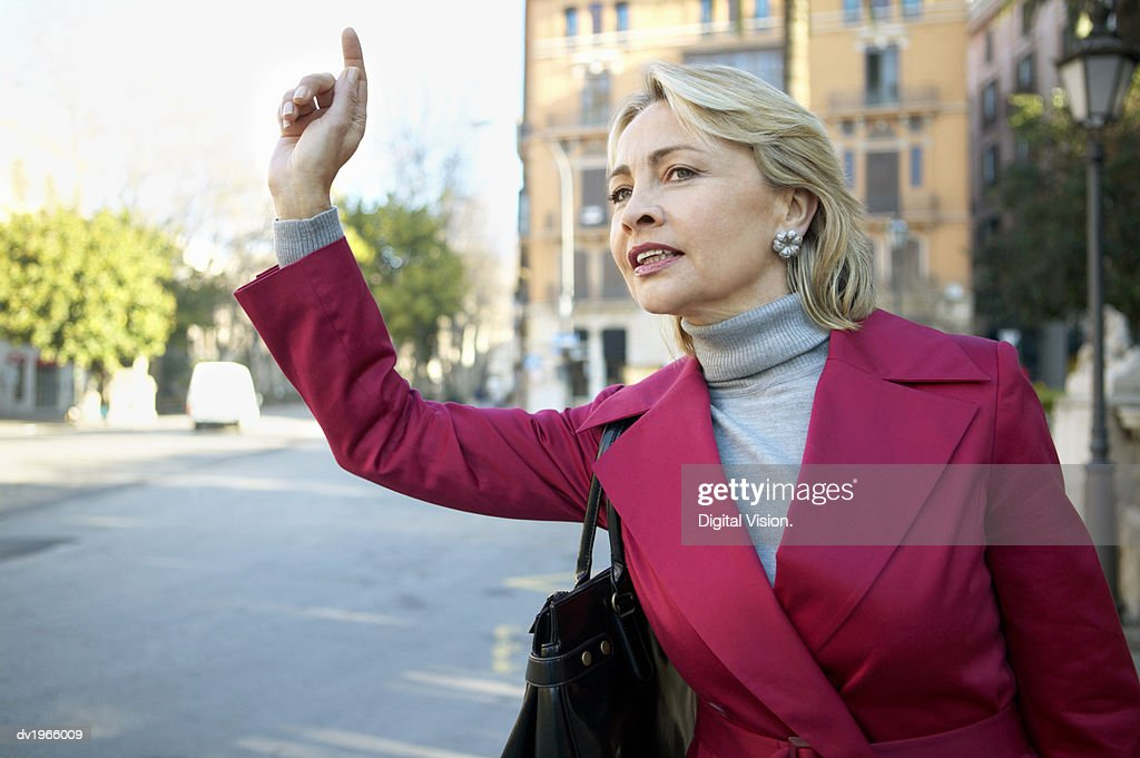 Businesswoman Standing Outdoors Hailing : Stock Photo
