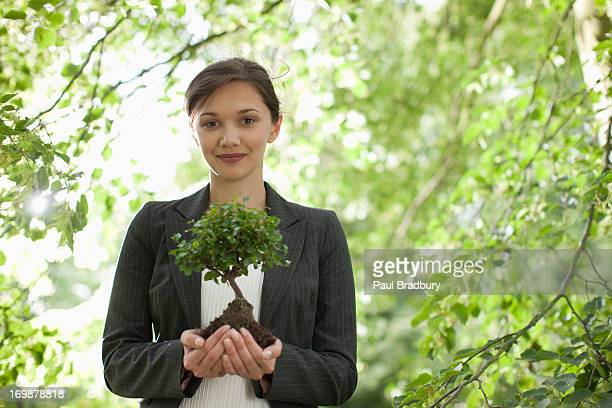 businesswoman standing outdoors holding plant - responsible business stock photos and pictures
