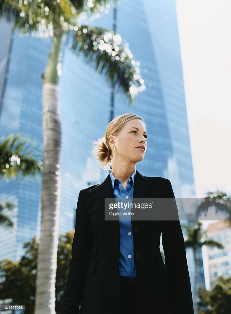 Businesswoman Standing Outdoors in a City Front of a Palm Trees : Stock Photo