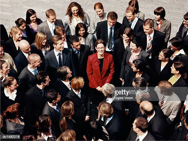 businesswoman standing outdoors surrounded by a large group of business people - surrounding stock pictures, royalty-free photos & images