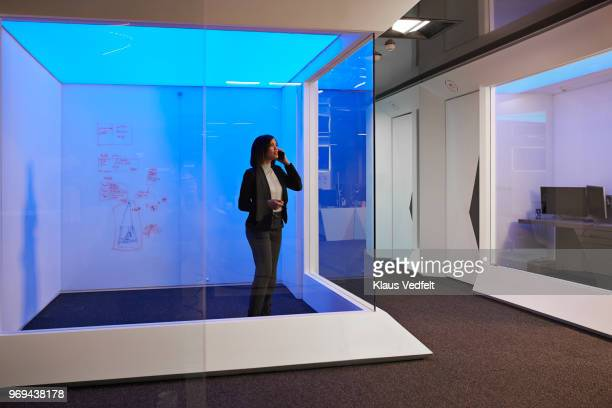 businesswoman standing & talking on phone in meeting room at corporate office - directrice photos et images de collection