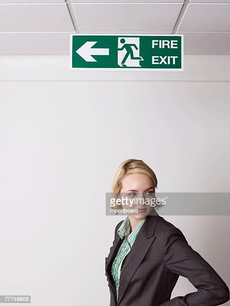 businesswoman standing under exit sign - evasión fotografías e imágenes de stock