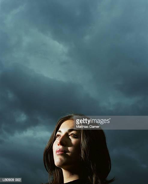Businesswoman standing under stormy sky, close-up, portrait