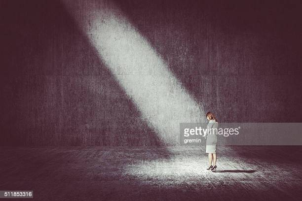 businesswoman standing under the spotlight - spotlit stock pictures, royalty-free photos & images