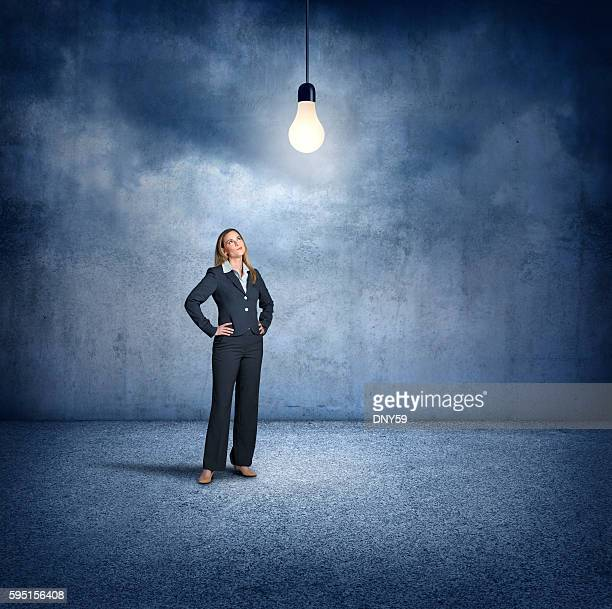 Businesswoman Standing While Looking Up At Lightbulb