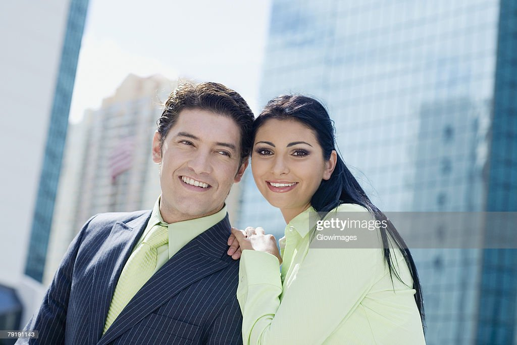 Businesswoman standing with a businessman and smiling : Foto de stock
