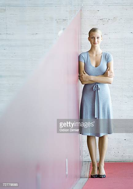 businesswoman standing with arms folded, full length - gray dress stock pictures, royalty-free photos & images