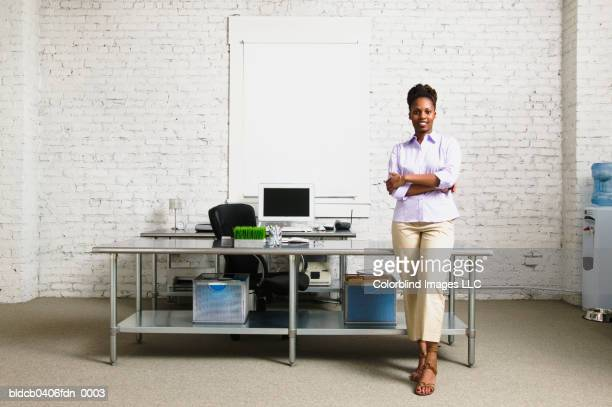 Businesswoman standing with arms folded leaning against a desk
