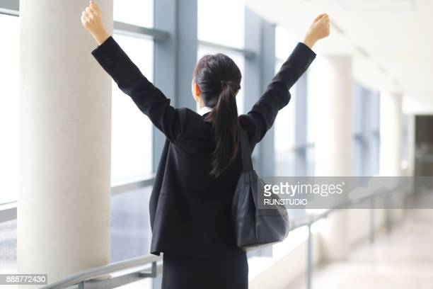 Businesswoman standing with arms raised in office corridor window