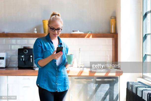 businesswoman standing with coffee mug in the kitchen looking at tablet - デニムシャツ ストックフォトと画像