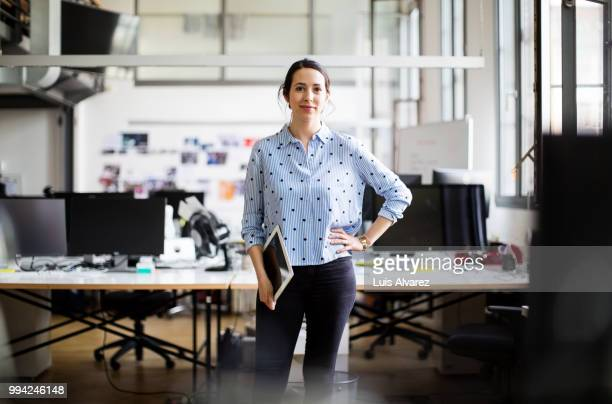 businesswoman standing with digital tablet - arbeitsstätten stock-fotos und bilder