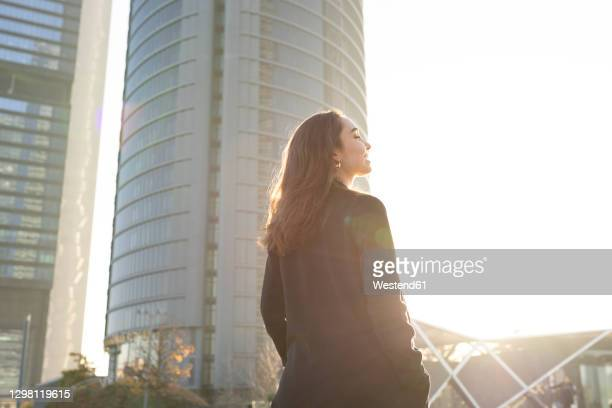 businesswoman standing with eyes closed and hand in pocket in city - 雰囲気 ストックフォトと画像