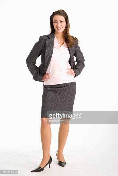 businesswoman standing with hands on hip, smiling, portrait - white skirt stock photos and pictures
